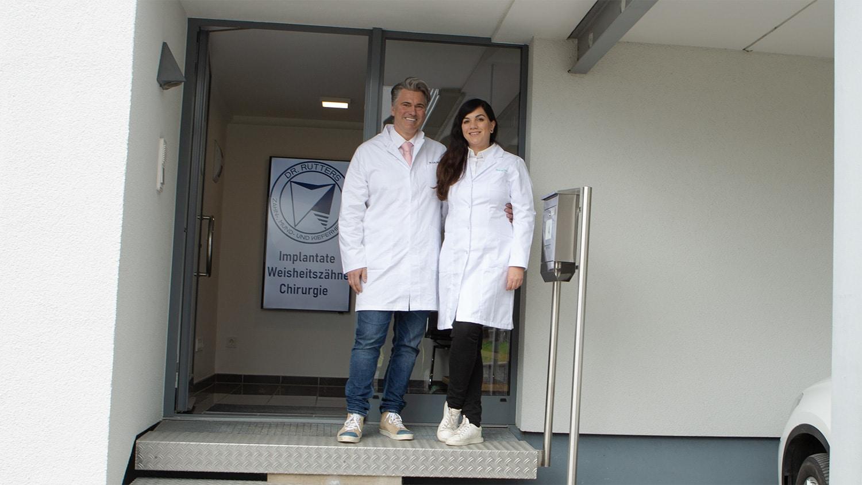 Frau und Herr Dr Rütters in Eingang Praxis für Zahn-, Mund- und Kieferheilkunde in Hachenburg